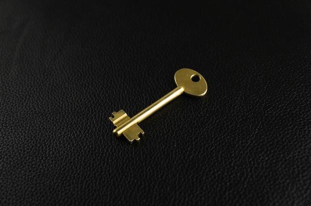 Złoty klucz na czarnej skórze