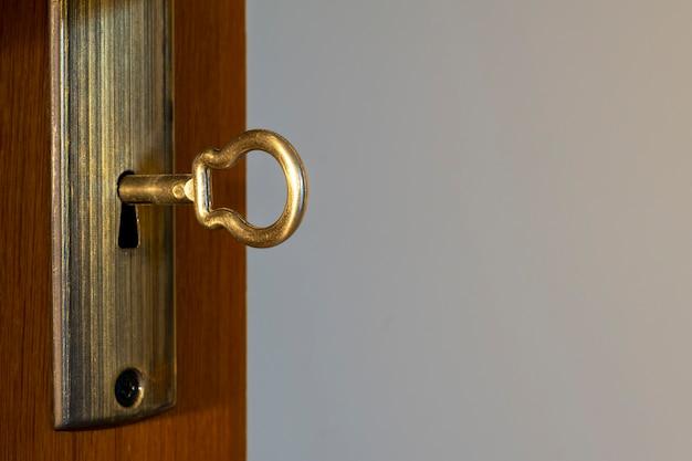 Złoty klucz w dziurkę od klucza, makro, jasne tło.