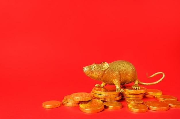 Złoty kolor szczura na stosie złotych monet z czerwonym tłem, chiński znak zodiaku szczura.