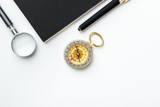 Złoty kompas z czarnym notatnikiem i piórem zamkniętymi up na stole