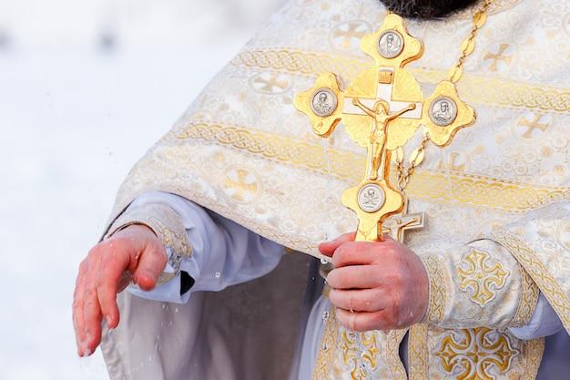 Złoty krzyż w rękach księdza z bliska. czas poświęcić wodę.