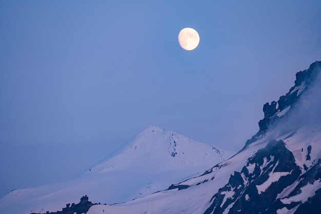 Złoty księżyc w pełni wznoszący się nad odległymi górami w niebieskiej godzinie