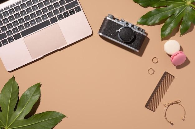 Złoty laptop na beżowym tle z zielonymi liśćmi. blog o urodzie. widok z góry, układ płaski. biurko w biurze domowym.