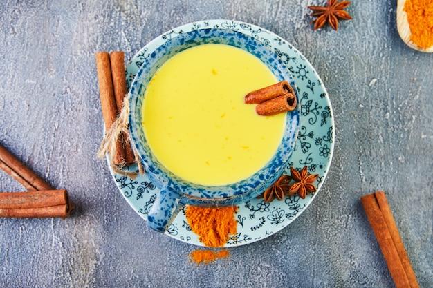 Złoty latte kurkuma zdrowy napój w niebieskiej filiżance.