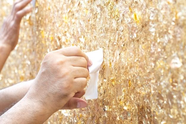 Złoty liść na tle ściany. ręce człowieka dołączyć złoty liść.
