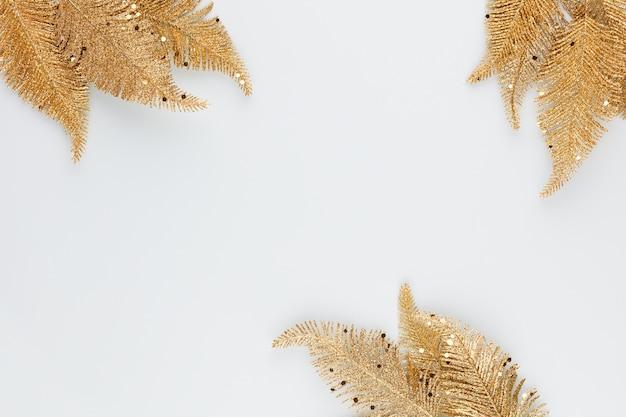 Złoty liść palmowy na niebieskim tle. liść palmowy, płaski układ i widok z góry.