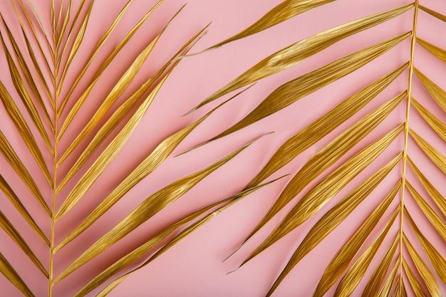 Złoty liść palmowy, tropikalny pozostawić teksturę na różowym tle. malowane złote liście roślin tropikalnych. lato deseń złotym tle kwiatów.