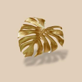 Złoty liść palmy tropikalnej monstera na pastelowym luksusowym żółto-szarym abstrakcyjnym wzorze do projektowania