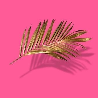 Złoty liść palmy tropikalnej na pastelowym luksusowym różowym abstrakcyjnym wzorze do projektowania i miejsca na tekst