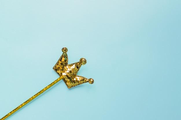 Złoty magiczny kij z cekinami w kształcie korony na pastelowym niebieskim tle. kreatywne mieszkanie leżało w minimalistycznym stylu