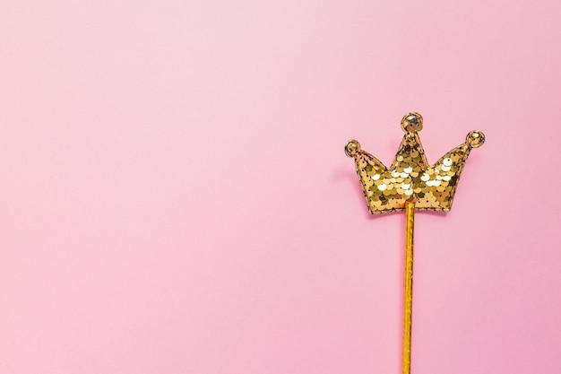 Złoty magiczny sztyft z cekinami w kształcie korony na pastelowym różowym tle. kreatywne mieszkanie leżało w minimalistycznym stylu. skopiuj miejsce na tekst