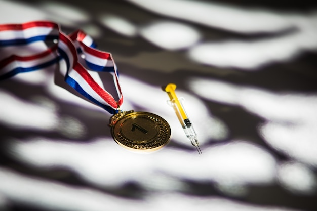 Złoty medal mistrza i strzykawka z substancją dopingującą ze światłami i cieniami wpadającymi przez okno. koncepcja sportu i dopingu