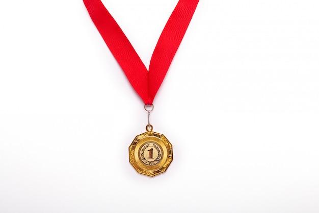 Złoty medal z czerwoną wstążką na białym tle. odosobniony.