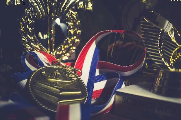 Złoty metal z czerwoną wstążką w kolorze białym i niebieskim, leżącym pomiędzy trofeami