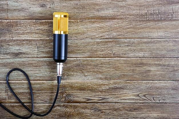Złoty mikrofon pojemnościowy z kablem leży na drewnianym stole z miejscem na kopię. motyw muzyczny. leżał na płasko. widok z góry.