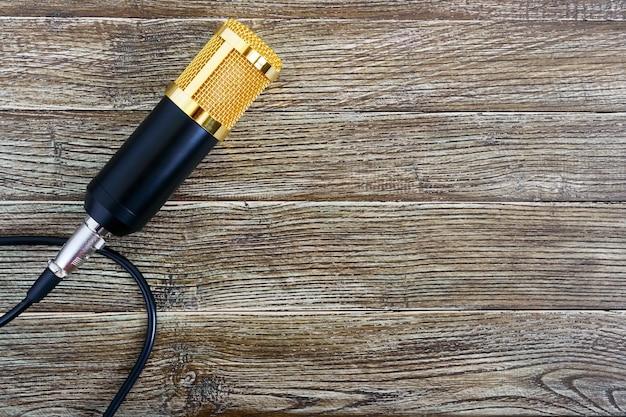 Złoty mikrofon pojemnościowy z kablem na drewnianym stole z miejscem na kopię. motyw muzyczny. leżał na płasko. widok z góry.