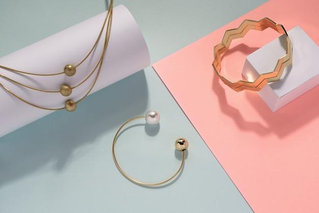 Złoty naszyjnik i bransoletki na różowym i niebieskim tle. złoty naszyjnik, perła i zygzakowate bransoletki w pastelowych kolorach.