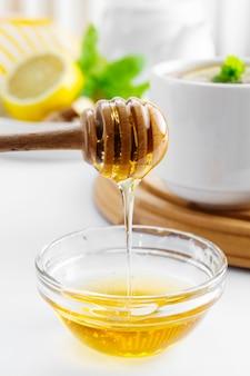 Złoty naturalny miód jesień zima gorący napój składnik szkło miska miodowa łyżka sezonowe