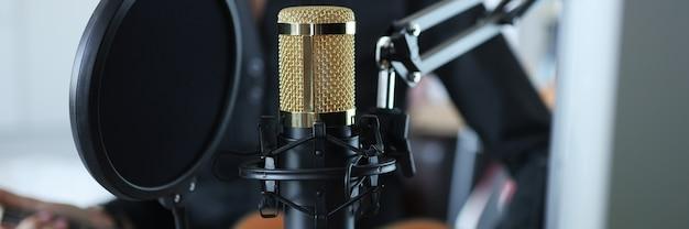 Złoty nowoczesny profesjonalny mikrofon studyjny zbliżenie tła