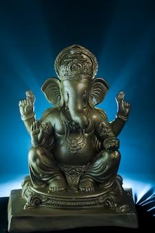 Złoty pan ganesha sclupture na ciemnym tle. świętować festiwal lord ganesha.