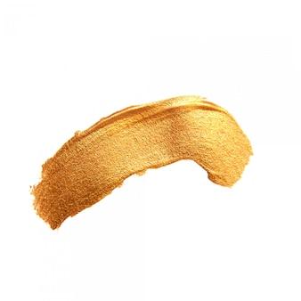 Złoty pędzel malowany akrylem. błyszcząca tekstura backgroundd złota plama na białym tle
