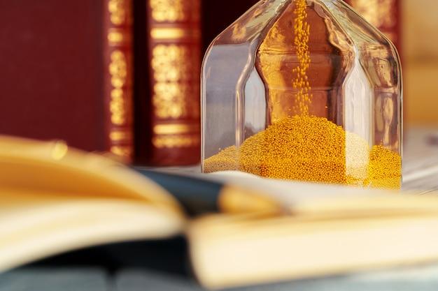 Złoty piasek klepsydry z bliska na stole roboczym
