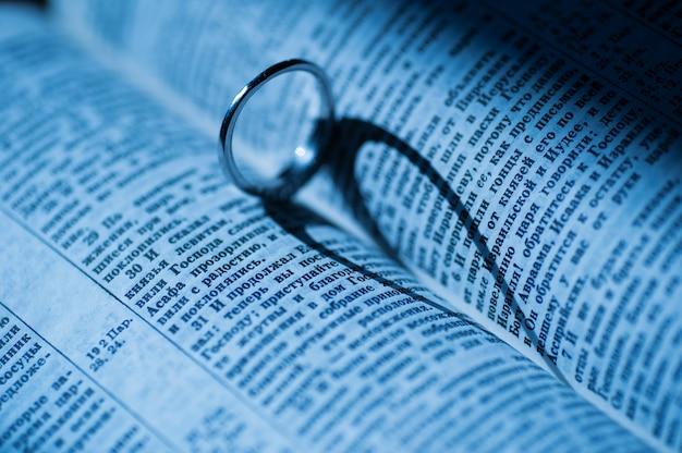 Złoty pierścień tworzy cień w kształcie serca w książce