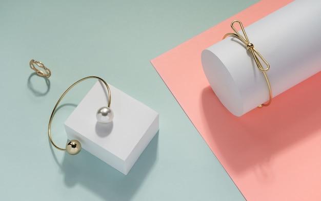 Złoty pierścionek i bransoletki na różowym i błękitnym papierowym tle. akcesoria złote dziewczyny na pastelowym kolorze tła.