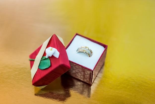 Złoty pierścionek w czerwonym pudełku prezentowym na złotym tle