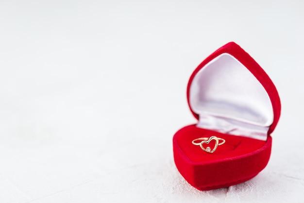 Złoty pierścionek w kształcie serca w czerwonym pudełku.
