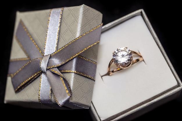 Złoty pierścionek w pudełku na białym tle na czarnej powierzchni
