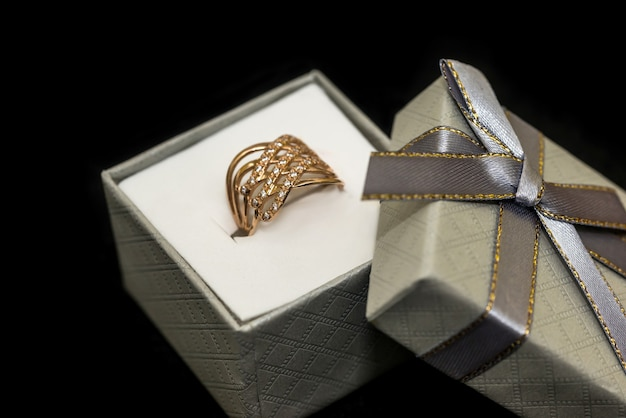 Złoty pierścionek w pudełku na czarnym tle