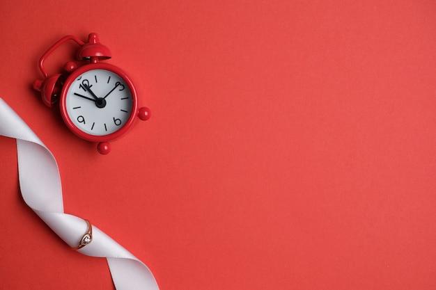 Złoty pierścionek z białą wstążką i zegarem na czerwonej przestrzeni. widok z góry.