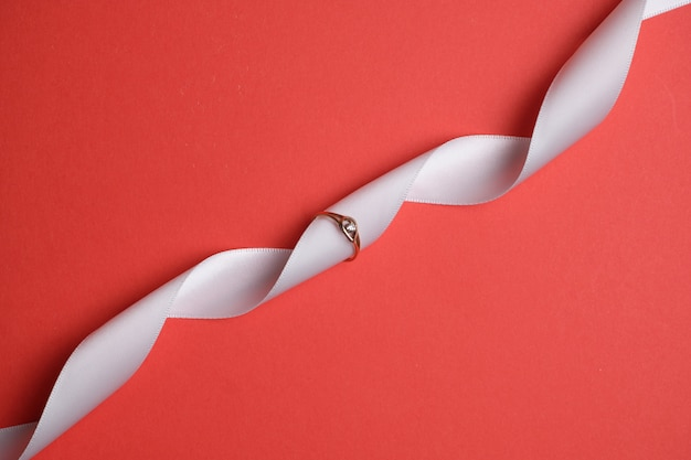 Złoty pierścionek z białą wstążką na czerwonej przestrzeni. widok z góry.