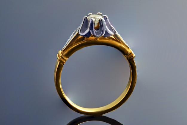 Złoty pierścionek z białego i żółtego złota z brylantami na gradientu i refleksji. produkcja biżuterii