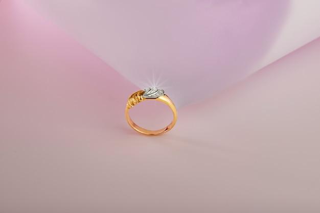 Złoty pierścionek z brylantami na różowym tle