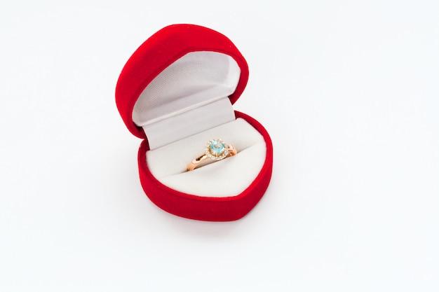 Złoty pierścionek z brylantem w czerwonym pudełku