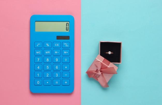 Złoty pierścionek z brylantem w ozdobnym pudełku i kalkulator na niebieskim pastelowym kolorze