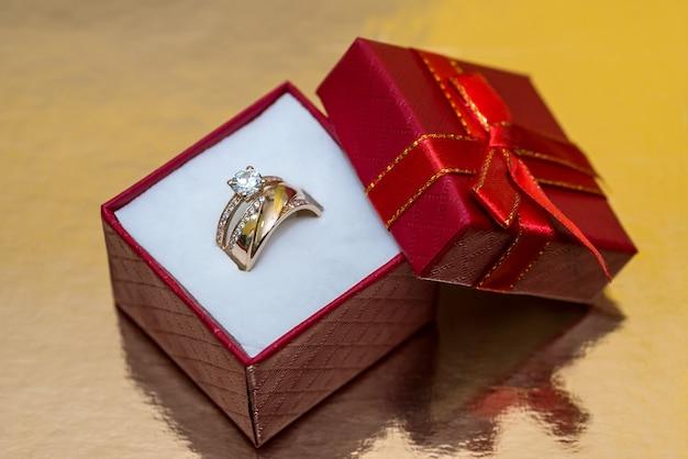 Złoty pierścionek z koroną w czerwonym pudełku