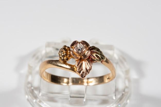 Złoty pierścionek z małym brylantem. rama w kształcie liści winogron na wzór black hills