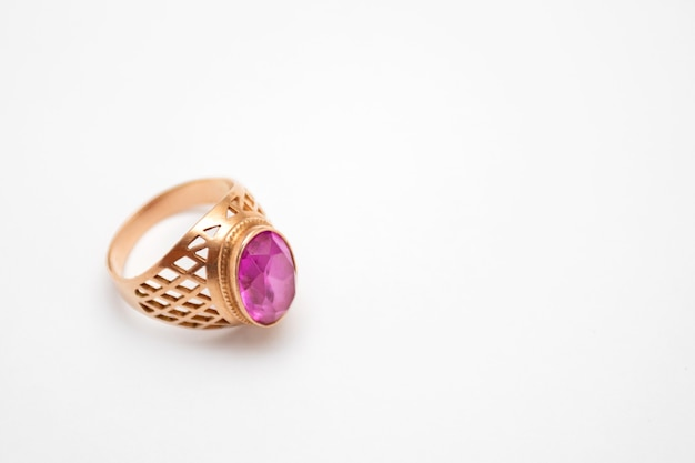 Złoty pierścionek z rubinem na białym tle