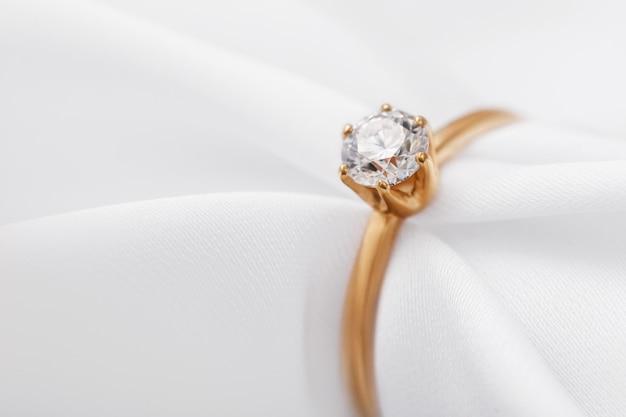Złoty pierścionek zaręczynowy z brylantem na jedwabnej tkaninie