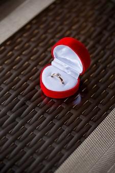 Złoty pierścionek zaręczynowy ze szlachetną biżuterią dla dziewczynki w czerwonym pudełku
