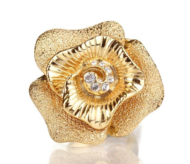 Złoty pierścionek ze złotym kwiatem i przezroczystymi kryształkami na białym tle