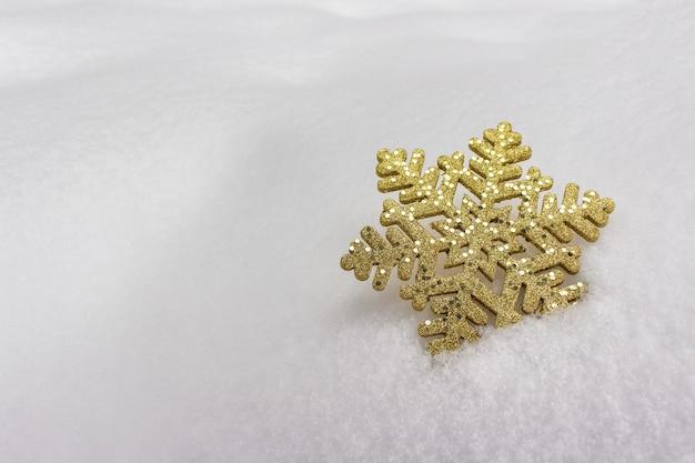 Złoty płatek śniegu z iskierkami na prawdziwym zimowym śniegu