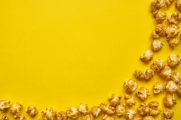 Złoty popcorn karmelowy zbliżenie. żółte tło popcornu. przekąski do filmu