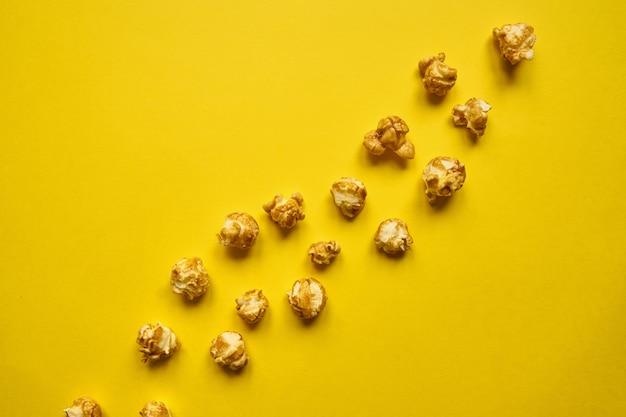 Złoty popcorn z karmelem na żółtym tle.