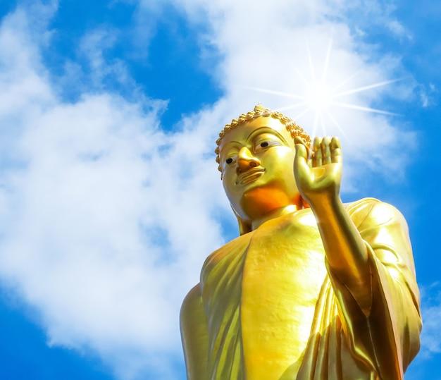 Złoty posąg buddy na zewnątrz na tle błękitnego nieba.