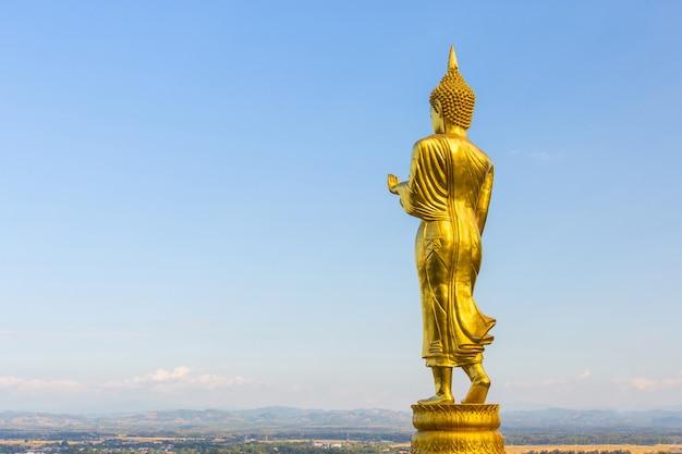 Złoty posąg buddy w świątyni phra that khao noi nan w tajlandii