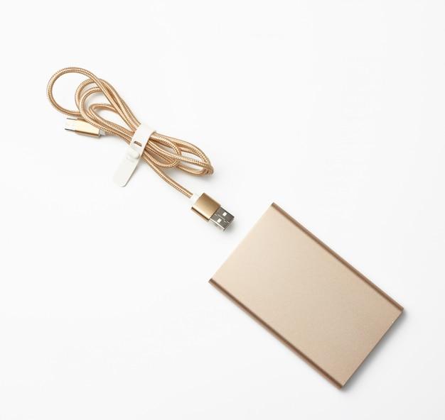 Złoty power bank i przewód ze złączem usb do ładowania urządzeń mobilnych na białej powierzchni